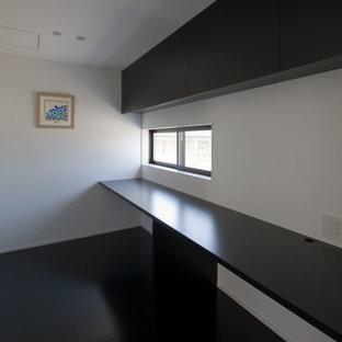 他の地域の広いモダンスタイルのおしゃれな書斎 (白い壁、クッションフロア、暖炉なし、造り付け机、黒い床) の写真