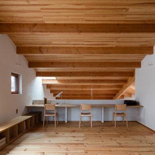 他の地域のビーチスタイルのおしゃれなホームオフィス・仕事部屋 (白い壁、造り付け机、茶色い床、淡色無垢フローリング) の写真