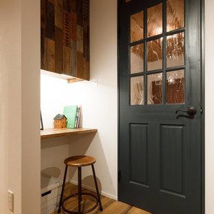 他の地域の小さいインダストリアルスタイルのおしゃれなホームオフィス・仕事部屋 (白い壁、無垢フローリング、造り付け机、茶色い床) の写真