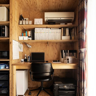 他の地域の小さいカントリー風おしゃれなホームオフィス・書斎 (茶色い壁、無垢フローリング、造り付け机、茶色い床) の写真