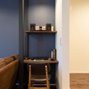 他の地域のミッドセンチュリースタイルのおしゃれなホームオフィス・仕事部屋 (青い壁、無垢フローリング、造り付け机、茶色い床) の写真