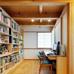 Inredning av ett asiatiskt hemmabibliotek, med vita väggar, ljust trägolv och ett inbyggt skrivbord