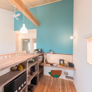他の地域の北欧スタイルのおしゃれなホームオフィス・書斎 (造り付け机、青い壁、無垢フローリング、茶色い床) の写真
