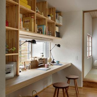 Bild på ett orientaliskt arbetsrum, med vita väggar, mellanmörkt trägolv, ett inbyggt skrivbord och brunt golv