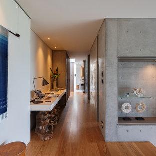 他の地域の広いコンテンポラリースタイルのおしゃれな書斎 (白い壁、無垢フローリング、暖炉なし、造り付け机、茶色い床) の写真