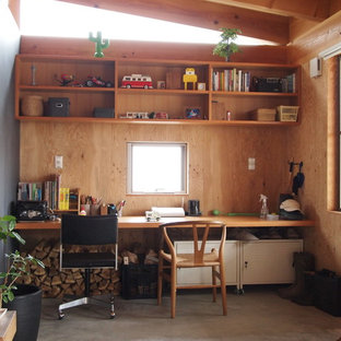 Inspiration for a small asian built-in desk concrete floor home office remodel in Other with brown walls