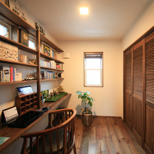 Design ideas for an asian home office in Other with white walls, medium hardwood floors, a built-in desk and brown floor.