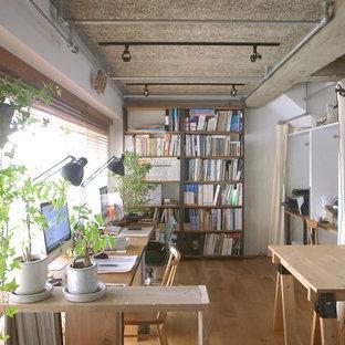 Réalisation d'un bureau nordique de type studio avec un mur blanc et un sol en bois brun.