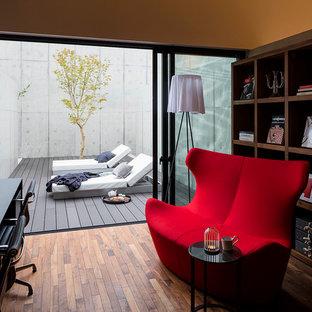 Cette image montre un bureau urbain avec un mur gris, un sol en bois brun et un bureau indépendant.