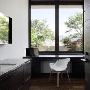 他の地域のモダンスタイルのおしゃれなホームオフィス・仕事部屋 (白い壁、濃色無垢フローリング、造り付け机、茶色い床) の写真