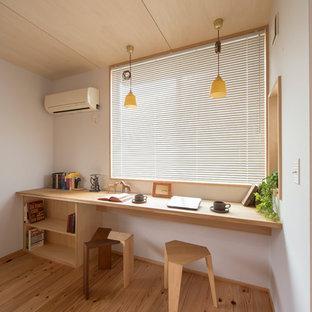 他の地域のアジアンスタイルのおしゃれなホームオフィス・書斎 (白い壁、無垢フローリング、造り付け机、茶色い床) の写真