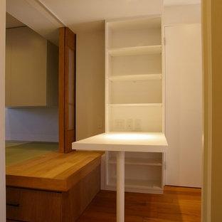 Foto di un piccolo ufficio minimalista con pareti bianche, pavimento in compensato, scrivania incassata e pavimento marrone