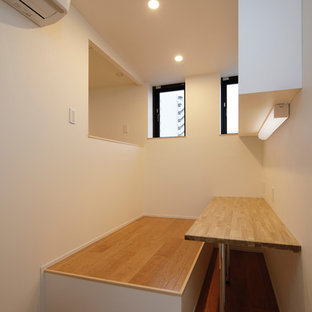 Immagine di un piccolo ufficio minimalista con pareti bianche, pavimento in legno verniciato, nessun camino, scrivania incassata e pavimento beige