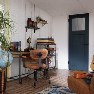 Esempio di uno studio industriale con pareti bianche, pavimento in legno verniciato, scrivania autoportante e pavimento marrone