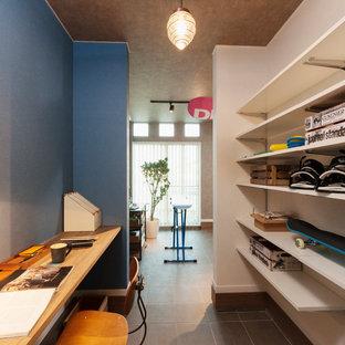 他の地域の中サイズのインダストリアルスタイルのおしゃれなアトリエ・スタジオ (青い壁、暖炉なし、造り付け机、茶色い床) の写真