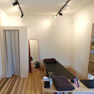 Foto di una sala pesi scandinava con pareti bianche, parquet chiaro e pavimento beige