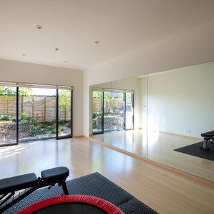 Esempio di una palestra multiuso minimalista con pareti bianche, parquet chiaro e pavimento beige