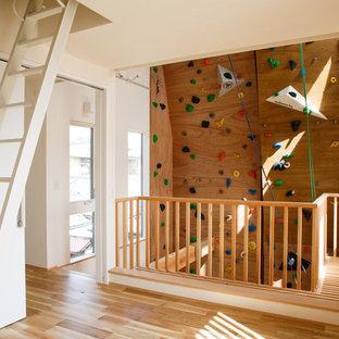 Moderner Fitnessraum mit Kletterwand, brauner Wandfarbe, braunem Holzboden und braunem Boden in Kyoto