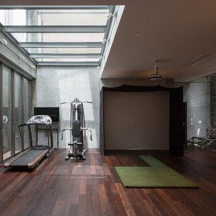 Esempio di un'ampia sala pesi design con pareti grigie, parquet scuro e pavimento marrone