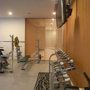 東京23区の巨大なモダンスタイルのおしゃれなトレーニングルーム (白い壁、リノリウムの床、グレーの床) の写真