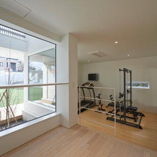 Foto di una sala pesi nordica con pareti bianche e pavimento in legno massello medio
