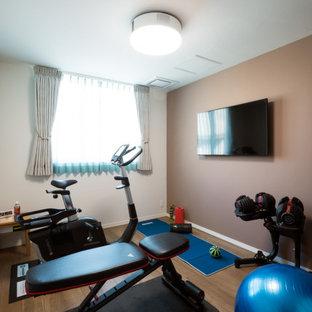 Esempio di una sala pesi nordica di medie dimensioni con pareti beige, pavimento in compensato e pavimento beige
