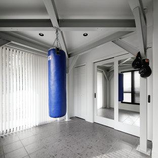 Cette image montre une salle de musculation minimaliste avec un mur blanc et un sol gris.