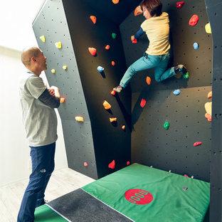 Ispirazione per una parete da arrampicata design con pareti nere e parquet chiaro