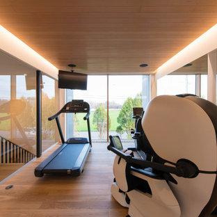 Großer Moderner Kraftraum mit weißer Wandfarbe, Sperrholzboden und braunem Boden