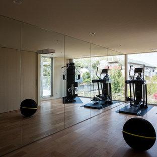 Ispirazione per una grande sala pesi minimalista con pareti beige e pavimento in legno massello medio