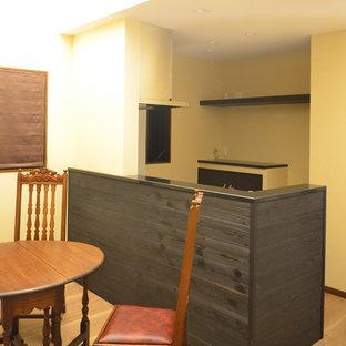 Idee per un angolo bar minimalista con lavello integrato, top in superficie solida, paraspruzzi nero, paraspruzzi in legno, pavimento in compensato, pavimento beige e top nero