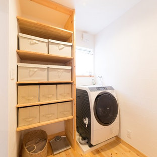 This is an example of a country utility room in Other with open cabinets, white walls, medium hardwood flooring, brown floors and an integrated washer and dryer.