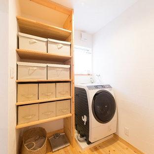 Foto di una lavanderia country con nessun'anta, pareti bianche, pavimento in legno massello medio, pavimento marrone e lavasciuga