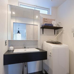 東京都下の小さいインダストリアルスタイルのおしゃれな家事室 (I型、アンダーカウンターシンク、オープンシェルフ、黒いキャビネット、人工大理石カウンター、白い壁、磁器タイルの床、グレーの床) の写真