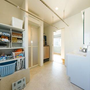 Immagine di una piccola lavanderia multiuso industriale con pavimento in compensato, pavimento beige, lavello integrato, ante lisce, ante bianche, top in superficie solida, pareti bianche e top bianco