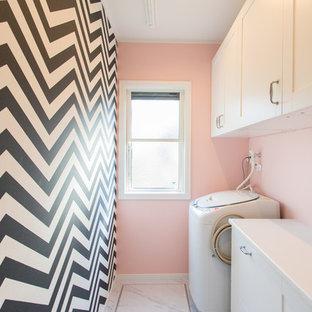 他の地域, の小さいビーチスタイルのおしゃれなランドリールーム (フラットパネル扉のキャビネット、白いキャビネット、ピンクの壁、グレーの床) の写真