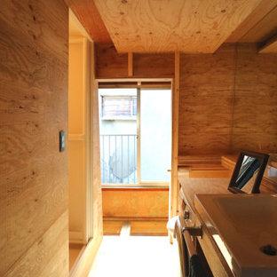 Bild på en liten funkis beige linjär beige liten tvättstuga, med en nedsänkt diskho, luckor med glaspanel, skåp i mörkt trä, träbänkskiva, beige stänkskydd, stänkskydd i trä, beige väggar, ljust trägolv och beiget golv
