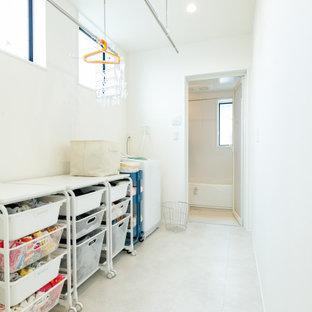 Minimalistisk inredning av en liten linjär tvättstuga enbart för tvätt, med vita väggar, vitt golv, öppna hyllor och vita skåp