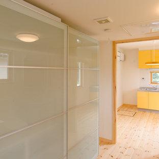 Exempel på en liten minimalistisk linjär liten tvättstuga med garderob, med luckor med glaspanel, vita skåp, vita väggar, ljust trägolv och beiget golv