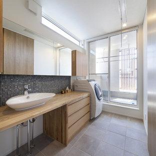 Cette image montre une buanderie urbaine avec un placard à porte plane, des portes de placard en bois clair, un plan de travail en bois, un mur blanc, un sol gris et le lave-linge et le sèche-linge forment un seul appareil électroménager.