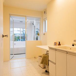 他の地域のアジアンスタイルのおしゃれなランドリールーム (一体型シンク、フラットパネル扉のキャビネット、白いキャビネット、ベージュの壁、ベージュの床、ベージュのキッチンカウンター) の写真