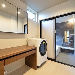 Esempio di una lavanderia moderna con ante lisce, ante in legno scuro, top in legno, pareti bianche, pavimento in legno verniciato, pavimento beige, top marrone e lavasciuga