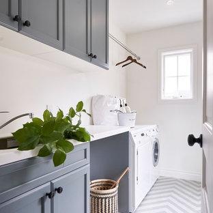 横浜のコンテンポラリースタイルのおしゃれな家事室 (アンダーカウンターシンク、グレーのキャビネット、人工大理石カウンター、白い壁、セラミックタイルの床、左右配置の洗濯機・乾燥機、マルチカラーの床、白いキッチンカウンター) の写真