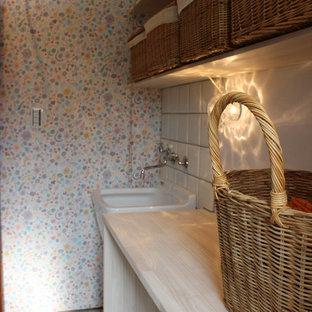 Foto på en liten lantlig vita tvättstuga enbart för tvätt, med träbänkskiva, vita väggar, vinylgolv, en tvättmaskin och torktumlare bredvid varandra och vitt golv