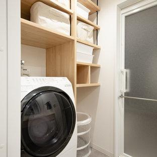 Industriell inredning av en mellanstor beige parallell beige tvättstuga enbart för tvätt och med garderob, med en nedsänkt diskho, öppna hyllor, skåp i ljust trä, träbänkskiva, beige väggar, laminatgolv och grått golv