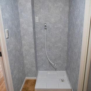 Modern inredning av en liten linjär tvättstuga enbart för tvätt och med garderob, med grå väggar, korkgolv och brunt golv