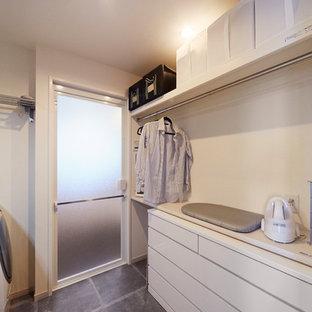他の地域の北欧スタイルのおしゃれなランドリールーム (白いキャビネット、白い壁、コンクリートの床、グレーの床、白いキッチンカウンター) の写真