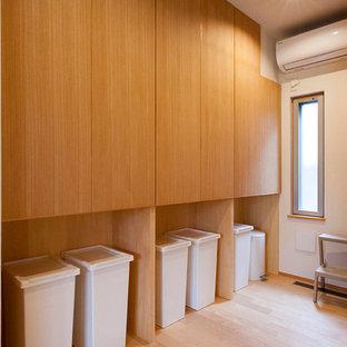 Immagine di una lavanderia multiuso country di medie dimensioni con ante a filo, ante in legno scuro, pareti bianche, pavimento in compensato, lavasciuga e pavimento beige