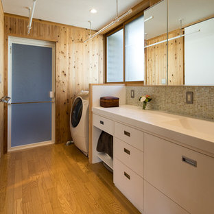 Idee per una lavanderia multiuso country di medie dimensioni con lavello integrato, ante a filo, ante bianche, top in superficie solida, pareti marroni, pavimento in compensato, lavasciuga, pavimento marrone e top bianco