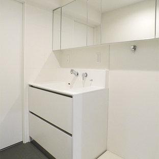 Exempel på en mellanstor 50 tals tvättstuga, med släta luckor, vita skåp, bänkskiva i koppar, linoleumgolv och grått golv